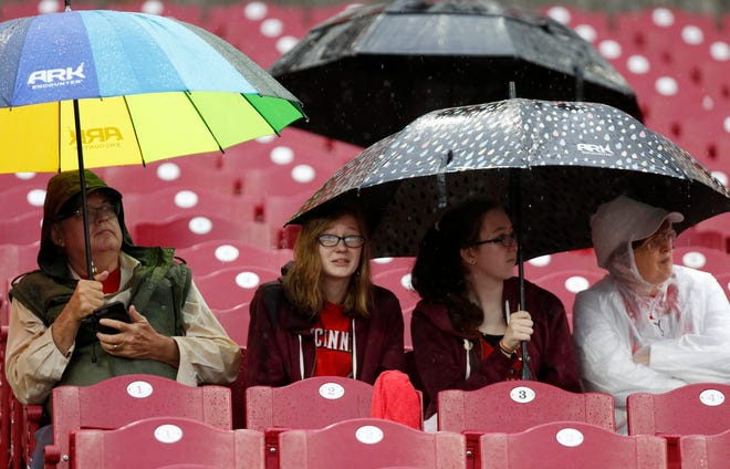 Fans sit under cover during a rain delay during a game between the San Diego Padres and the Cincinnati Reds.