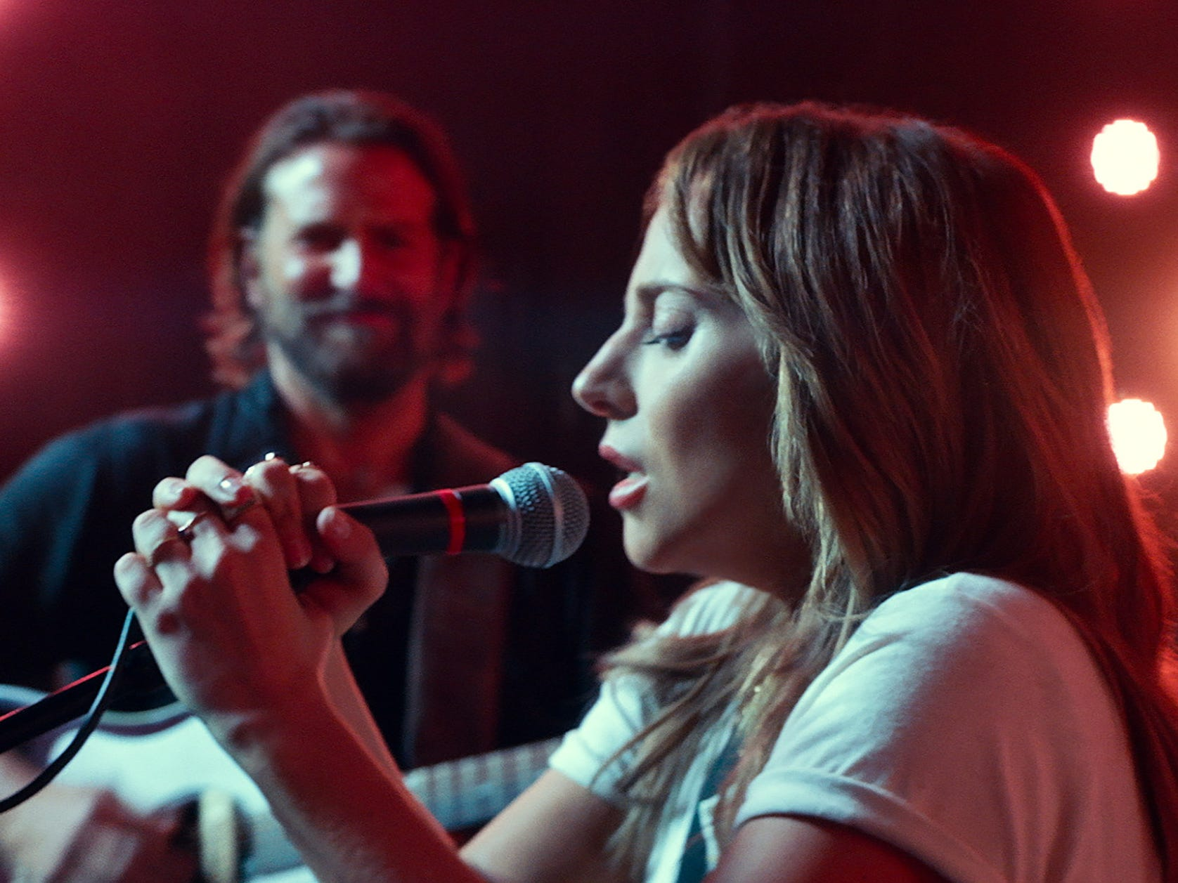 "Ally (Lady Gaga) sings and Jackson (Bradley Cooper) backs her up in ""A Star Is Born."""