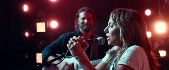 """Ally (Lady Gaga) sings and Jackson (Bradley Cooper) backs her up in """"A Star Is Born."""""""