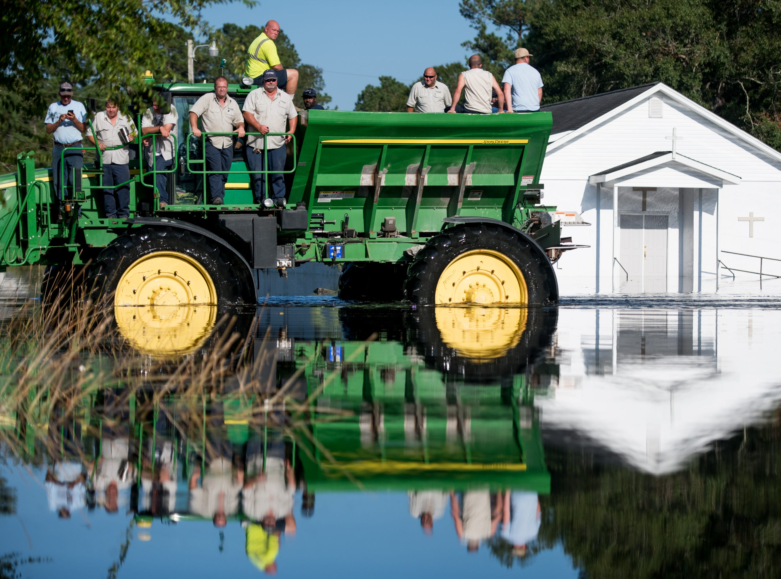 Workers uses farm machinery to navigate floodwaters from the Waccamaw River caused by Hurricane Florence on Sept. 26, 2018 in Bucksport, S. C.
