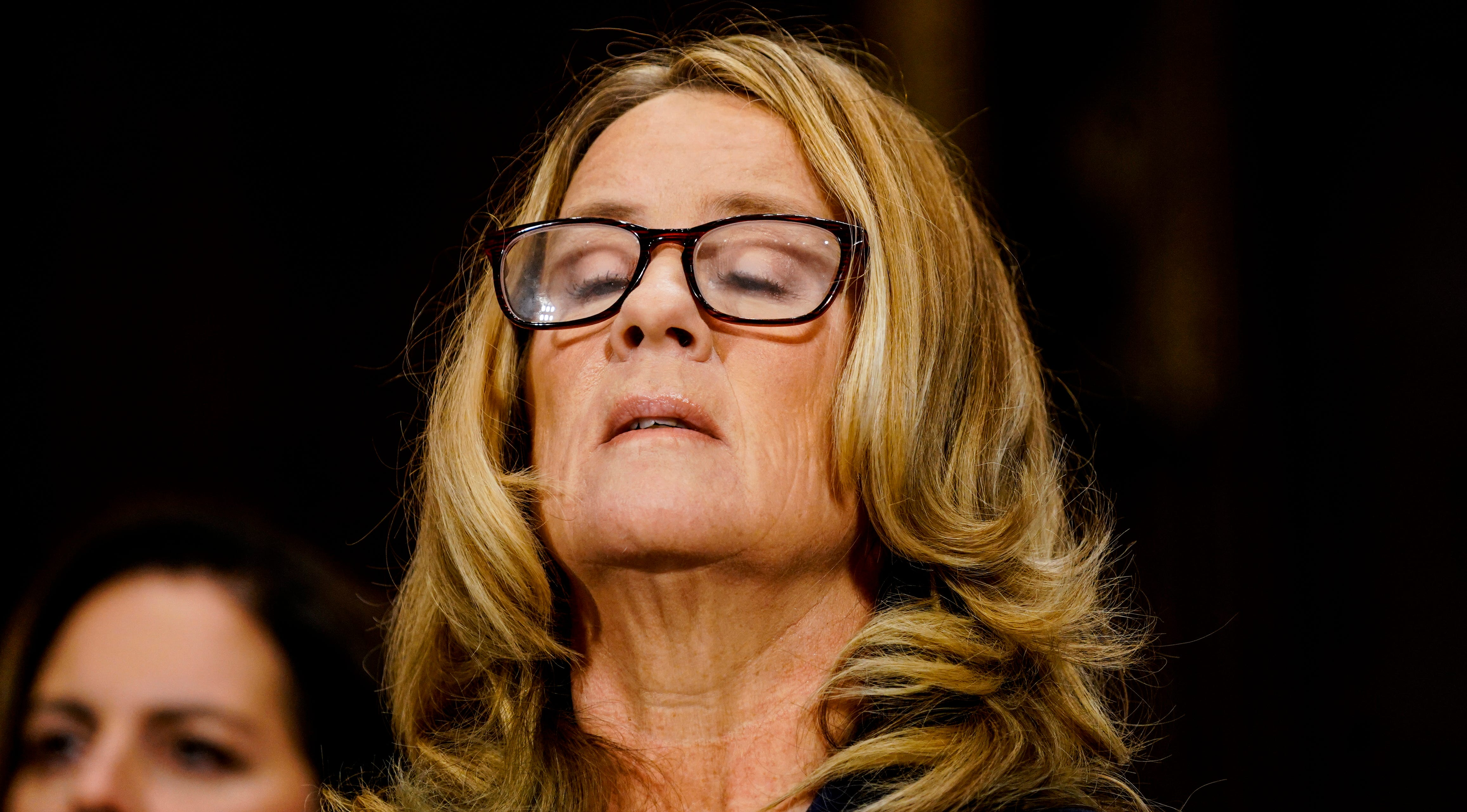 Christine Blasey Ford takes a breath at a Senate Judiciary Committee hearing in the Dirksen Senate Office Building.