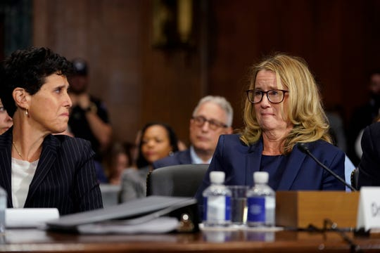 Christine Blasey Ford becomes emotional as she listens to Sen. Cory Booker, D-N.J., as she testifies before the Senate Judiciary Committee on Capitol Hill in Washington, Thursday, Sept. 27, 2018. At left is attorney Debra Katz. (AP Photo/Andrew Harnik, Pool) ORG XMIT: DCAH247