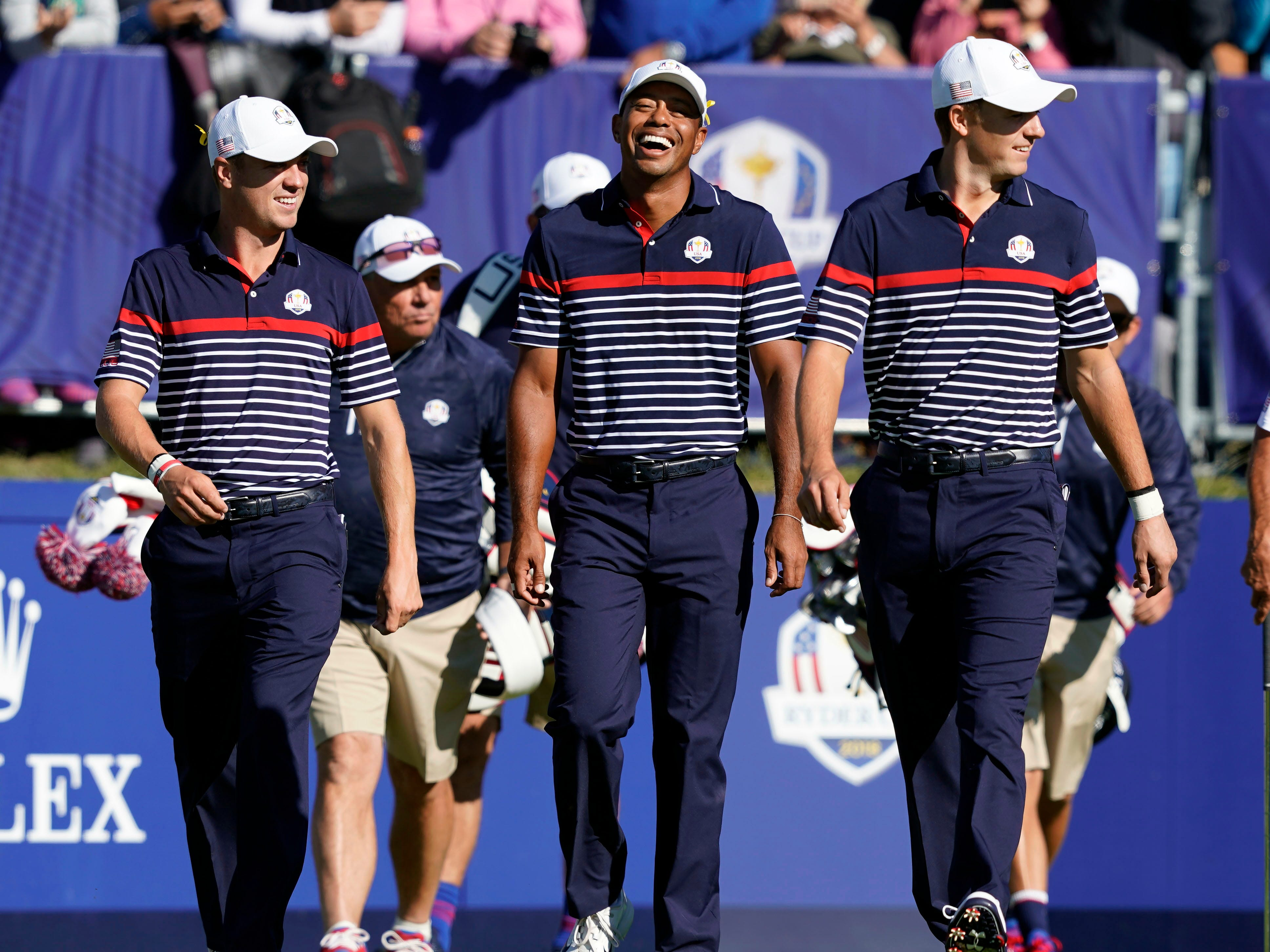 Tiger Woods throws his head back laughing as he walks off the first tee with Justin Thomas and Jordan Spieth during a practice round.