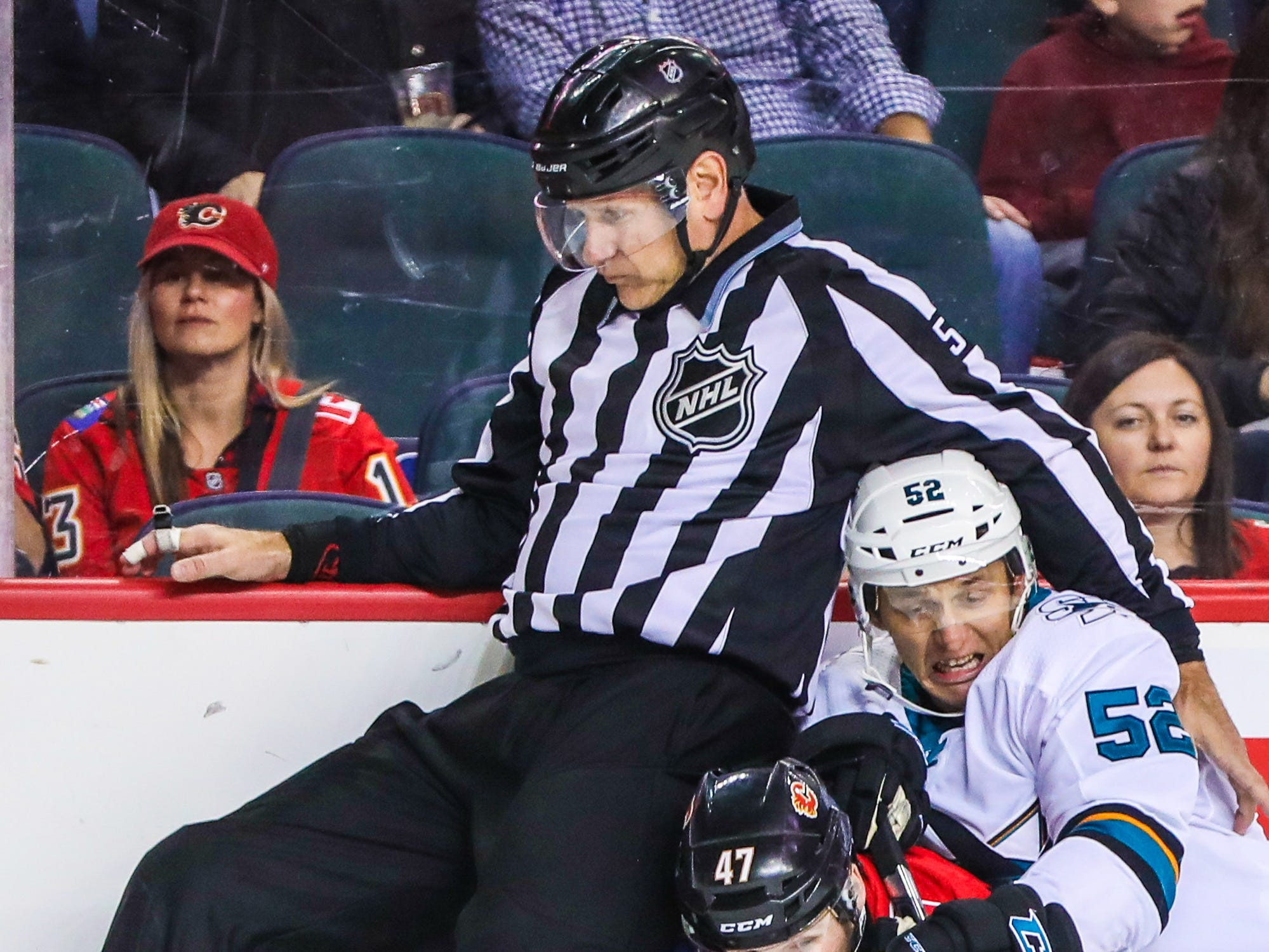 Sept 25: An NHL on-ice official tries to get out of the way as Calgary Flames right wing Matthew Phillips and San Jose Sharks center Lukas Radil battle for the puck.