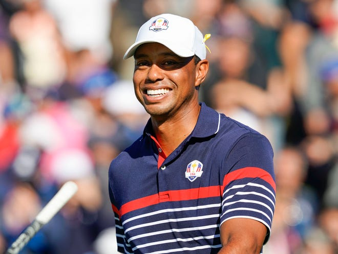 Tiger Woods smiles as he walks from the first tee during a Ryder Cup practice round.