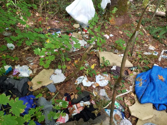 Garbage and debris left behind in encampment in Puyallup, Washington.