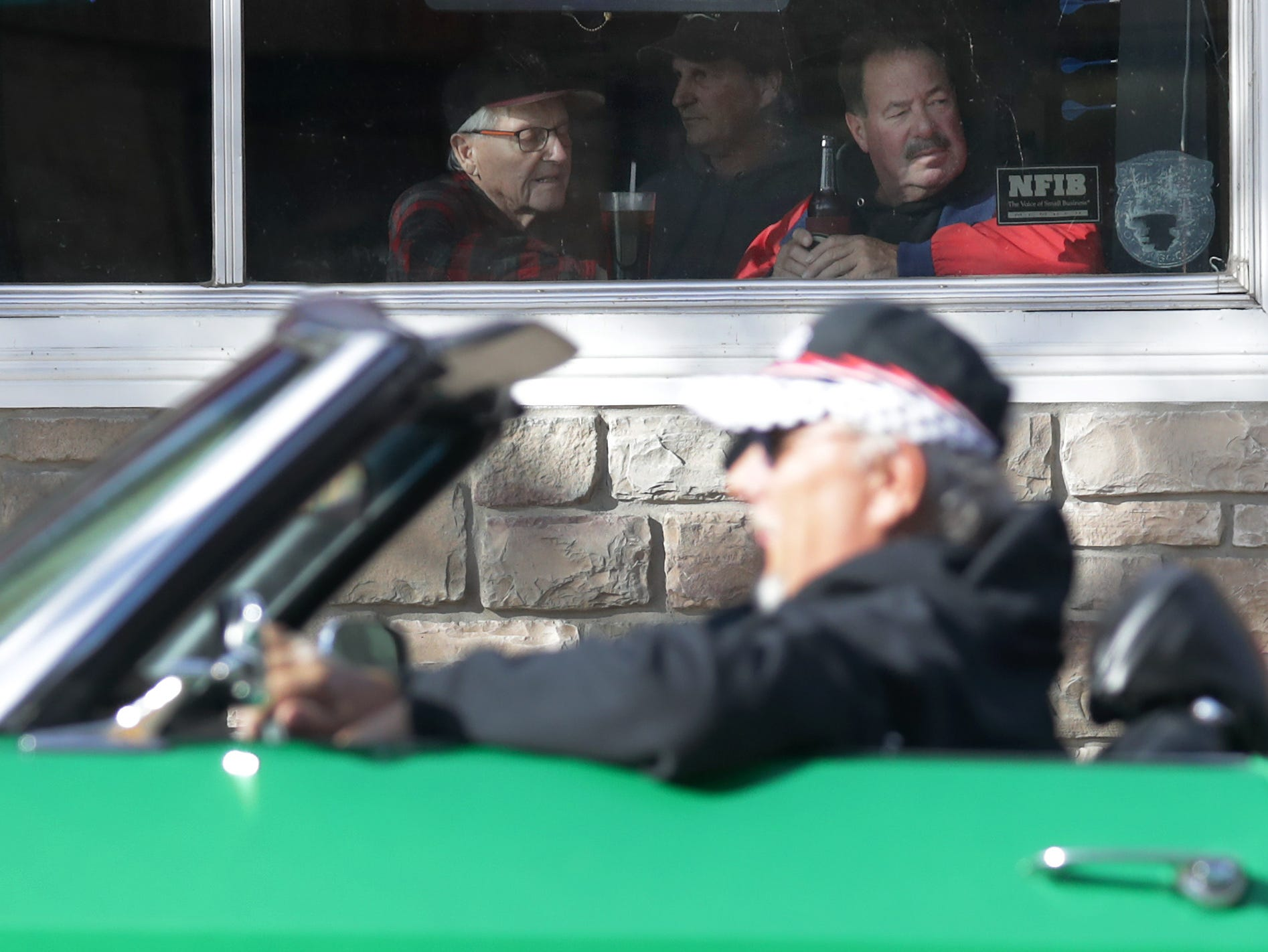 Patrons of Dr. Jekyll's watch as cars pass by during the annual License to Cruise car show on Friday, September 28, 2018, on College Ave. in Appleton, Wis.