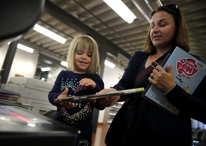 Allie Johnston, left, helps her mother Tracy Johnston, of Appleton, check books out of the Kaukauna Public Library last fall. The Kaukauna Public Library is one of the sites across the Fox Cities that will host events for the Fox Cities Book Festival.