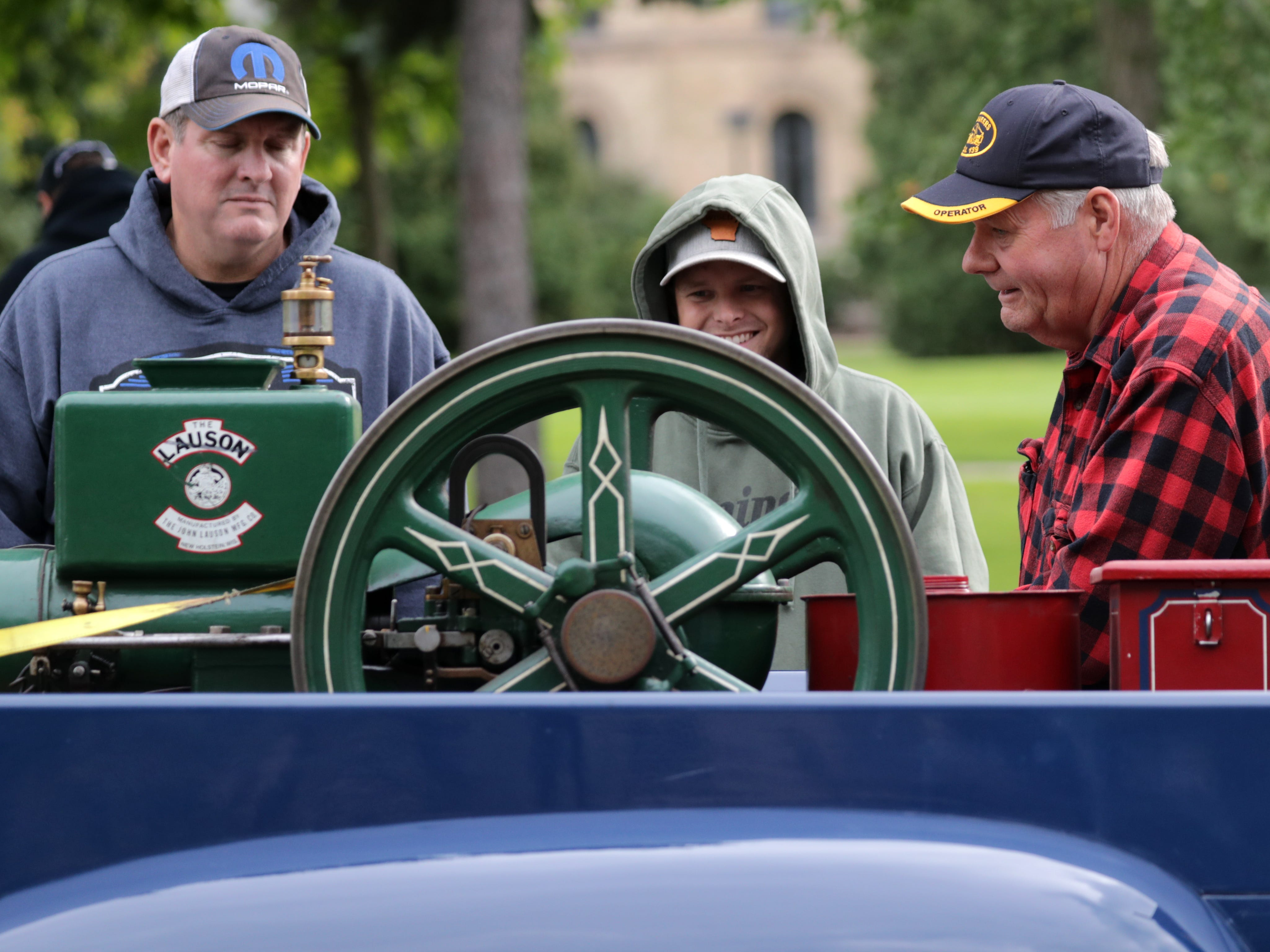 Ross Goldbeck, right, talks about his New Holstiein made Lauson engine with Jeff Thurk, left, Goland Ryan Hayes, center during the annual License to Cruise car show on Friday, September 28, 2018, on College Ave. in Appleton, Wis.