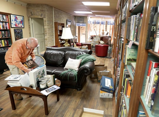 Owner Tom Lyons stocks bookshelves in at Lyons Books in downtown Neenah. The store opens Tuesday.