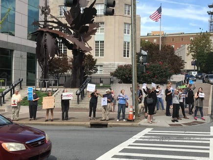 About 25 people gathered outside the Federal Building on Patton Avenue at midday Friday to protest the prospect that Brett Kavanaugh may be confirmed to the U.S. Supreme Court.