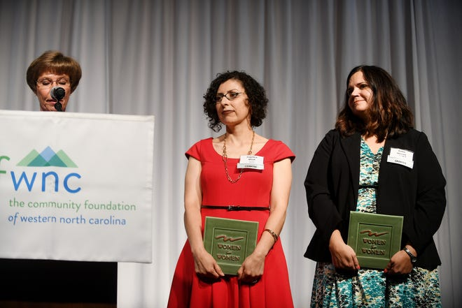 Angelica Wind, center, holds a plaque as Women For Women Giving Circle announces a $450K collaborative high-impact grant to Buncombe Partners in Prevention, a collaborative organization that includes Helpmate, Mountain Child Advocacy Center, Our VOICE and Pisgah Legal Services at Power of the Purse May 22, 2018.