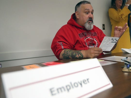 """Jason Gomez asks a participant for three transportation tickets at the """"Employer"""" station during the re-entry simulation. Gomez, a chemical dependency counselor, went through re-entry in real life."""