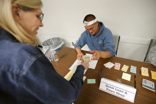 """Daniel DeCoteau, of the Port Gamble S'Klallam Tribe, plays the part of a pawn shop employee and hands Judy Dutcher, the Washington regional coordinator for Bridges To Life, some """"cash."""" The tribe sponsored the re-entry simulation."""
