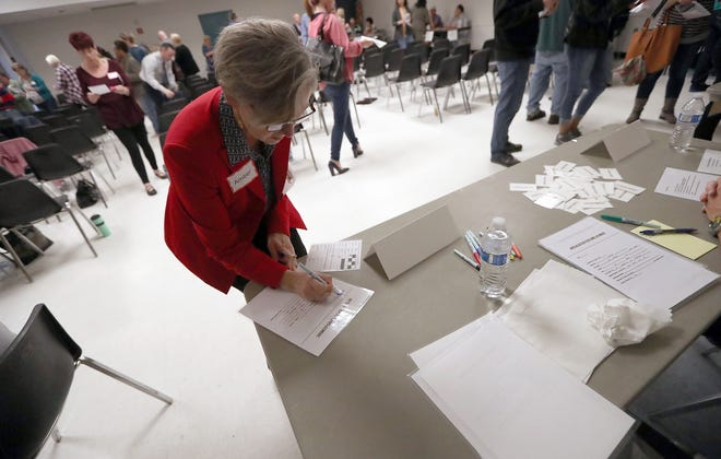 Kitsap County Prosecutor Tina Robinson fills out a job application during a re-entry simulation event at the Givens Community Center in Port Orchard on Friday. The event provided lessons in the difficulties faced by people attempting to reintegrate into society after a jail term.
