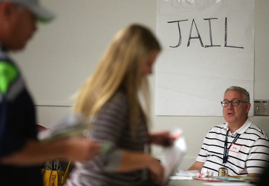"Mike Canonica, from the state Division of Child Support, sits in the jJail"" during the reentry simulation at the Givens Community Center in Port Orchard on Friday."
