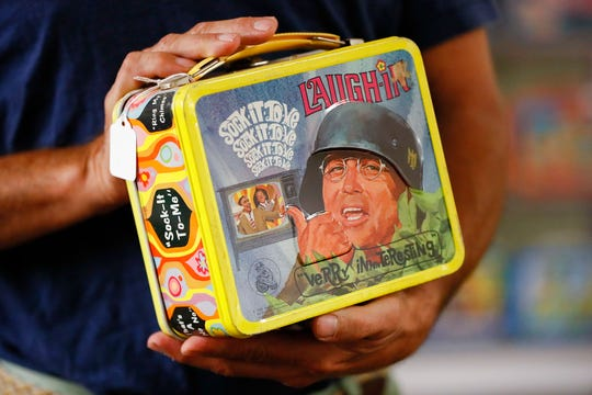 In this Friday, Sept. 21, 2018 photo, a vintage lunch box is handled at Main Auction Galleries Inc., in downtown Cincinnati. Karp, a longtime auctioneer of Cincinnati-area estates has come upon a Baby Boomer delight: hundreds of vintage lunchboxes featuring the heroes of their childhood's comic books, TV shows, cartoon strips, movies and more. (AP Photo/John Minchillo)