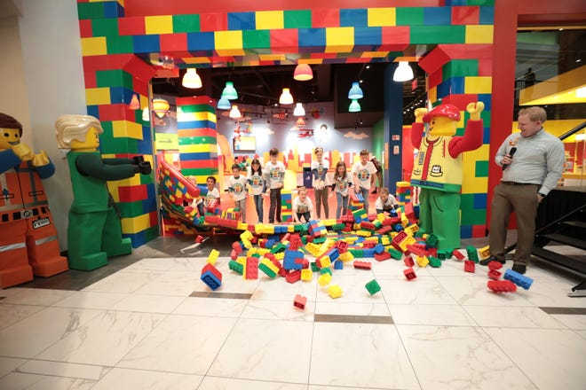 Kids knock down a LEGO brick wall during the grand opening of LEGOLAND Discovery Center Columbus