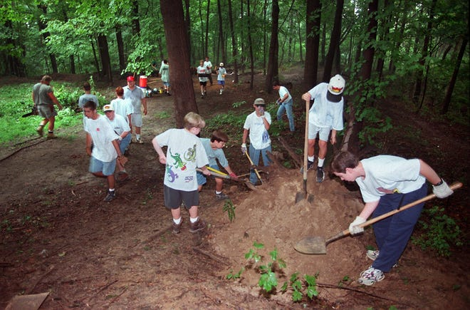 Volunteers work on filling holes made by people looking for Civil War souvenirs and cleared brush at the site of Battery Bates, one of 29 Civil War earthworks built to fend off a Confederate threat of attack in September 1862.