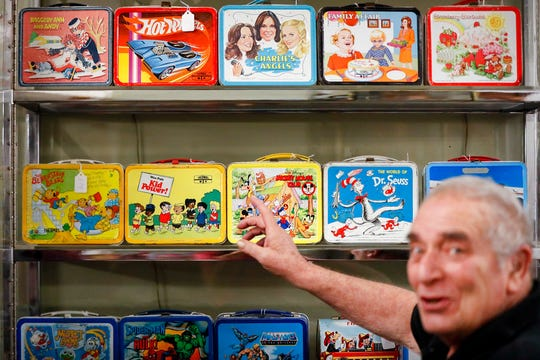 In this Friday, Sept. 21, 2018 photo, owner J. Louis Karp opens a case of vintage lunch boxes at Main Auction Galleries Inc., in downtown Cincinnati. Karp, a longtime auctioneer of Cincinnati-area estates has come upon a Baby Boomer delight: hundreds of vintage lunchboxes featuring the heroes of their childhood's comic books, TV shows, cartoon strips, movies and more.  (AP Photo/John Minchillo)
