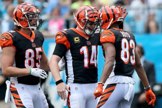 Cincinnati Bengals quarterback Andy Dalton (14), center, and Cincinnati Bengals tight end Tyler Eifert (85), left, congratulate Cincinnati Bengals wide receiver Tyler Boyd (83) on his touchdown catch in the third quarter during a Week 3 NFL game between the Cincinnati Bengals and the Carolina Panthers, Sunday, Sept. 23, 2018, at Bank of America Stadium in Charlotte, North Carolina. Carolina won 31-21.
