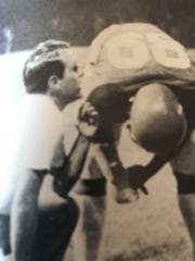 Bill Fridman instructs one of his players in the 1977 football season for the Mt. Healthy City School District.