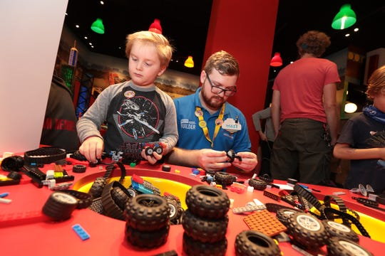 Maxx Davidson, a Ashland High School graduate and Master Model Builder at LEGOLAND Discovery Center, works with a child during the grand opening