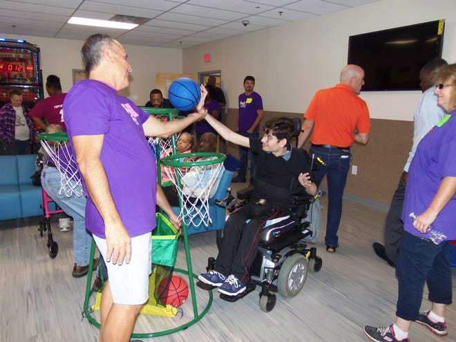 Community Access Unlimited member Joao Sialho gets an assist from a FedEx employee during the games portion of the day.