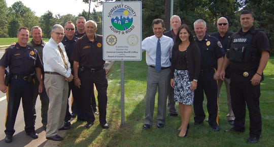 (Left to right) Capt. Mark Szczecina, Sheriff's Officer Dave Daneker, Montgomery Township Administrator Donato Nieman, Montgomery Lt. James Gill, Lt. Alan Santoro, Sheriff Frank Provenzano, Somerset County Freeholder Mark Caliguire, Col. Richard Borden, Montgomery Mayor Christine Madrid, Montgomery Capt. Thomas Wain, Col. Roy Gandolfe and Detective Giacomo Crismale stand with Montgomery's new Adopt-A-Road sign.
