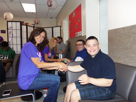 Community Access Unlimited members Giovanni  Mancini and James Maccia (second from right and right) receive hand massages from two FedEx volunteers at the Spa Day portion of the day.