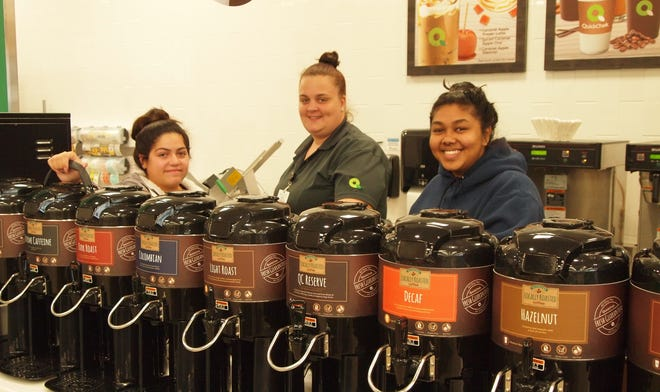 QuickChek Store Leader Alexandra Salazar, far left, and team members Casey Clark and Oma Sampal put the final preparations on QuickChek's famed coffee wall in the enhanced Raritan Borough opening on Oct. 2.