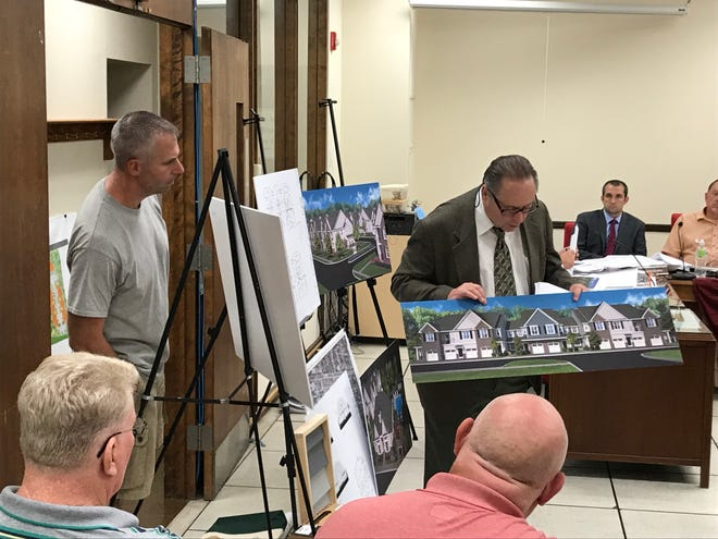 The architect for the Kirby Village apartment complex, which was just approved, at a Somerville Planning Board meeting holding a rendering of the apartments' design.
