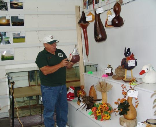Gourd judge Bruce Barber looks at decorative gourd birdhouse during the judging.