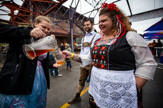 Beth Rodas, left, of Bondurant pours beers from the Golden Keg for Sheri Houdesheldt, right, and Dan Nilsen, both of Ankeny, to start the Des Moines' Oktoberfest Friday, Sept. 28, 2018.