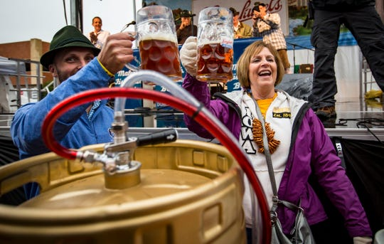 Cindy Kuker, right of Des Moines, gets the first beer from the Golden Keg to start the Des Moines' Oktoberfest Friday,  Sept. 28, 2018. At left is C.J. Leinenkugel of Chippewa Falls, Wisc., sixth-generation of the beer brewing family.