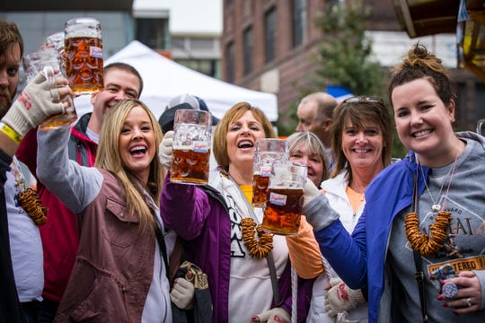 Patrons drink the first beers from the Golden Keg to start the Des Moines' Oktoberfest Friday, Sept. 28, 2018.
