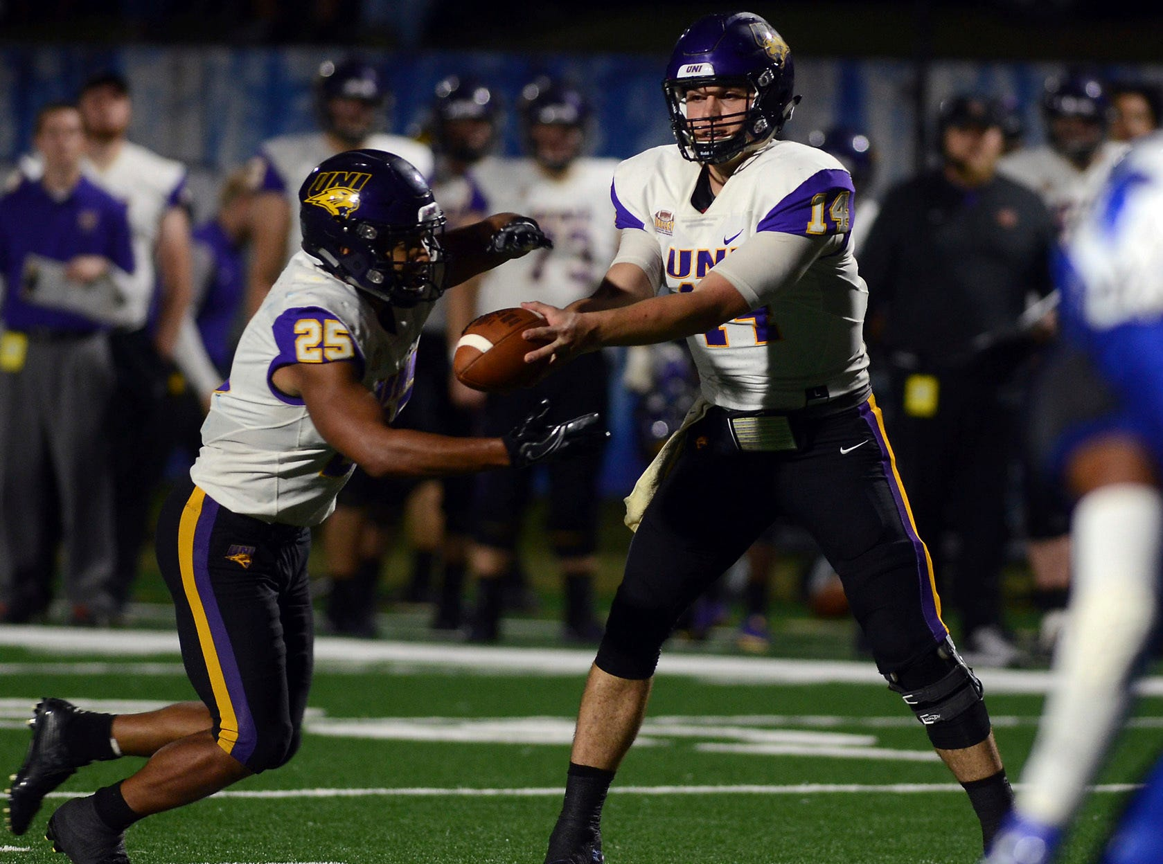 Northern Iowa's Eli Dunne, right, hands the ball off to Trevor Allen during the team's NCAA college football game against Indiana State on Thursday, Sept. 27, 2018, in Terre Haute, Ind.