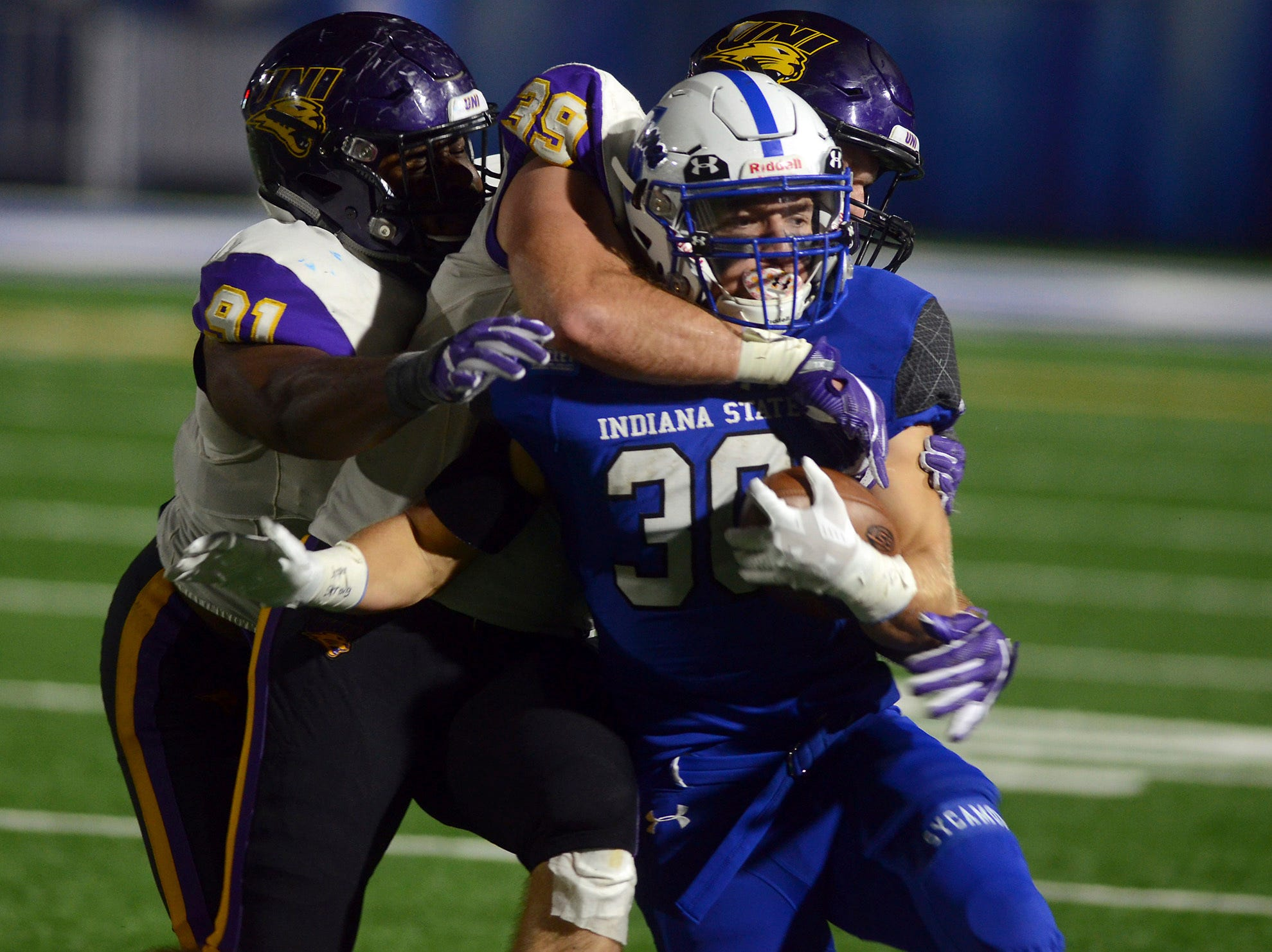 Indiana State running back Titus McCoy is wrapped up by two Northern Iowa defenders during an NCAA college football game Thursday, Sept. 27, 2018, in Terre Haute, Ind.