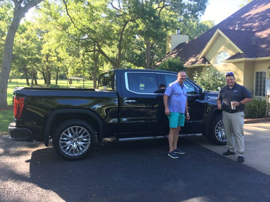 Mike Herron, left, with his 2019 GMC Sierra Denali and Gilchrist Automotive salesman David Bryson.