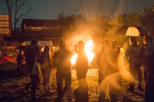 Partygoers gather around a bonfire  in drizzling rain as a freight train passes by during a full moon party at Lincoln Street Art Park in Detroit on Monday, Sept. 24, 2018. The monthly events are held on or around the full moon and often include performances and DJs.