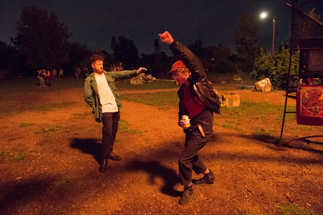 Mike Meadow of Detroit, left, and Cruce Grammatico of Detroit, right, dance during a full moon party at Lincoln Street Art Park in Detroit on Monday, Sept. 24, 2018. The monthly event went on despite soggy weather, attracting a hardy few to listen to a DJ and enjoy themselves by a bonfire.