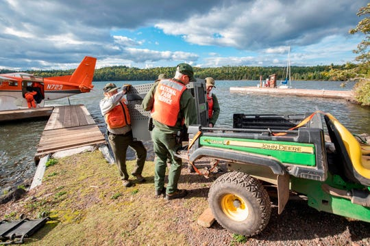 This Wednesday, Sept. 26, 2018, photo provided by the National Park Service shows NPS staff unloading a crated gray wolf from a United States Fish & Wildlife Service aircraft at Isle Royale National Park in Michigan.