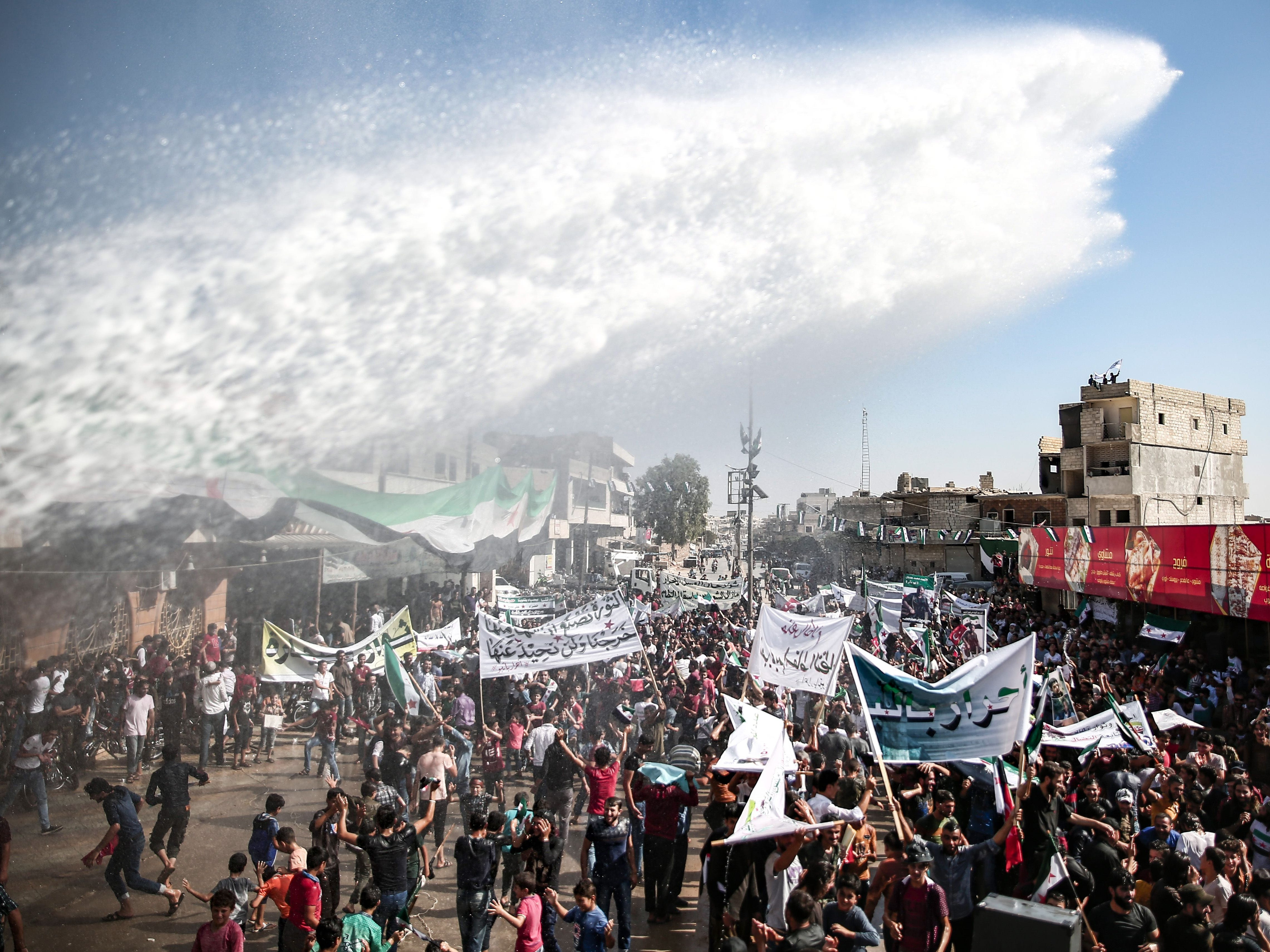 Water is sprayed to cool down Syrian protesters calling for the release of those held in its prisons, in the rebel-held town of Atareb, Aleppo, Syria, on Sept. 28, 2018.