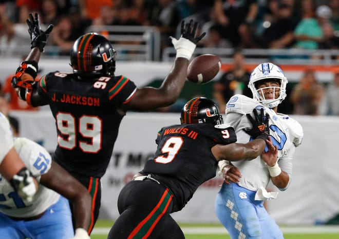 Miami defensive linemen Joe Jackson (99) and Gerald Willis III (9) rush North Carolina quarterback Chazz Surratt (12) as he attempts to pass during the first half on Thursday.