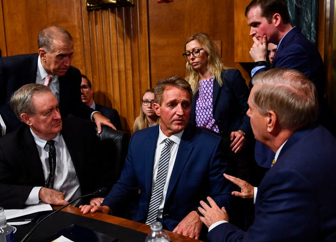 """Senate Judiciary Committee member Sen. Jeff Flake (R-AZ), center, speaks with colleagues after a hearing on Capitol Hill in Washington, DC on September 28, 2018, on the Supreme Court omination of Brett M. Kavanaugh.  Kavanaugh on Friday won the support of Flake, who said the judge was entitled to the """"presumption of innocence … absent corroborating evidence."""""""