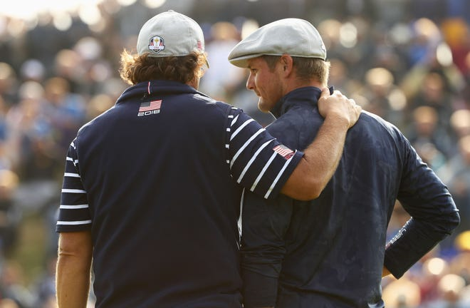 Phil Mickelson, left, chats with partner Bryson DeChambeau during their Ryder Cup loss on Friday afternoon.