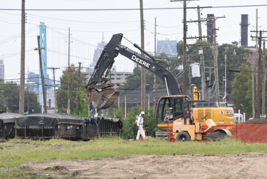 Workers clear land along West Jefferson Avenue and Schroeder Street in the Delray neighborhood in Detroit  Thursday. The land will be used for a truck and customs plaza for the Gordie Howe International Bridge.