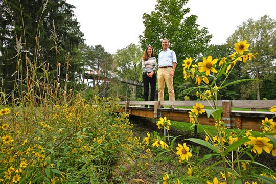 Elizabeth Lumbert, director of Dow Gardens, and Mike Whiting, president of the Herbert H. And Grace A. Dow Foundation,  enjoy the view from a small bridge in the new Canopy Walk in Dow Gardens' Whiting Forest in Midland.