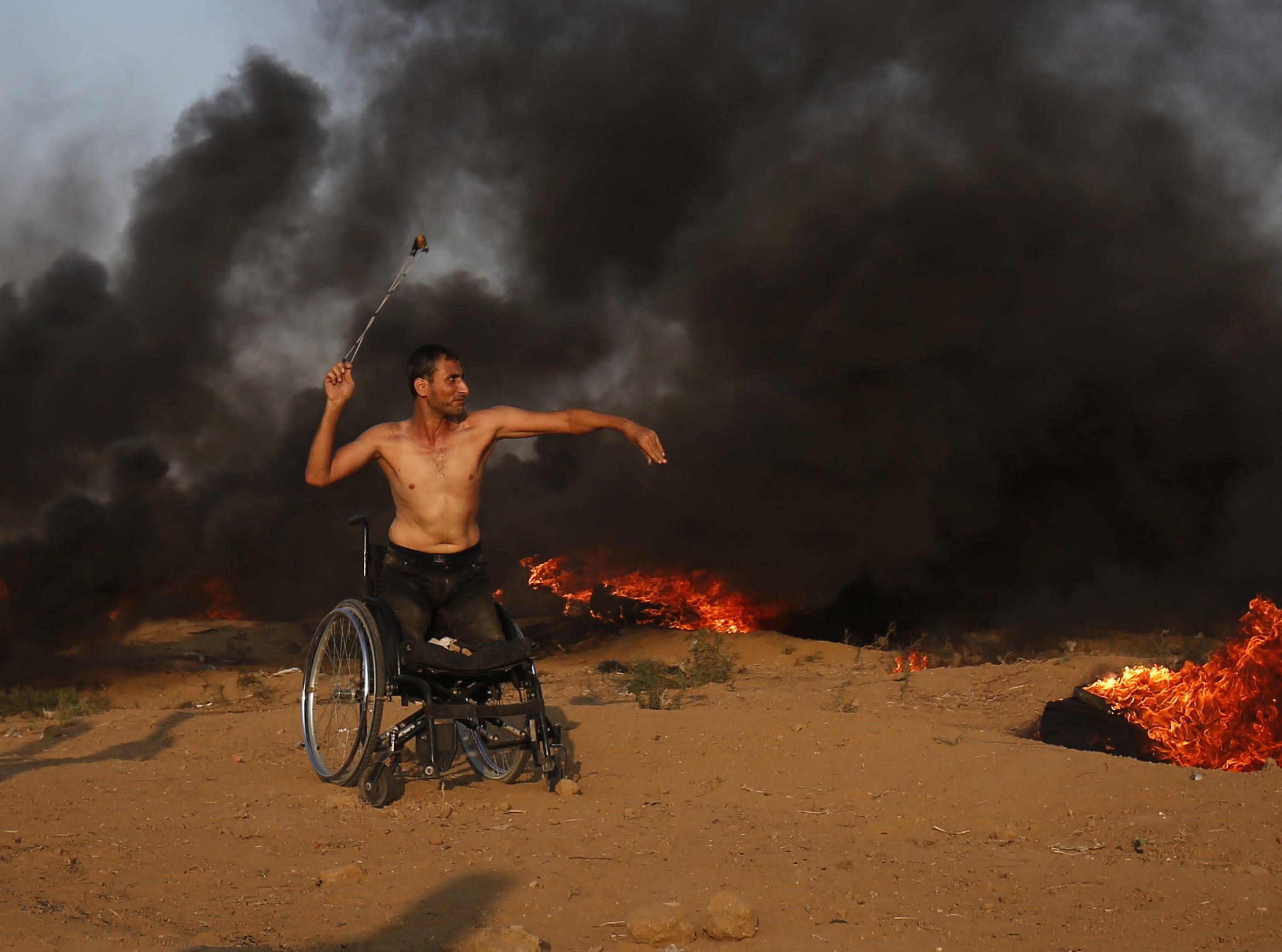A Palestinian protester in a wheelchair throws a stone toward Israeli forces during clashes along the Israeli border fence, east of Gaza City on Friday, Sept. 28, 2018.