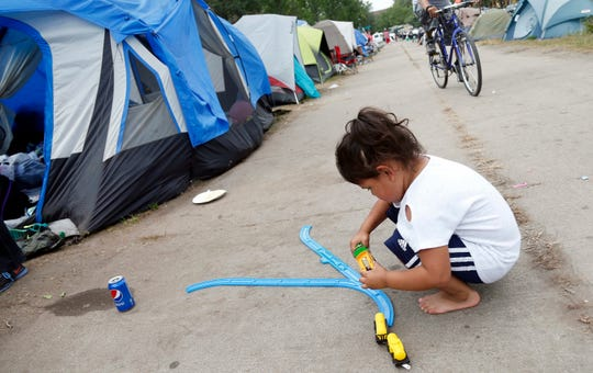 Koda Deer, 4, plays with a toy train set at a homeless encampment.